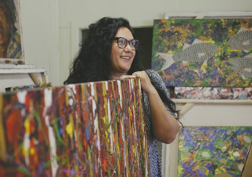 An Indigenous woman smiling in an art studio.
