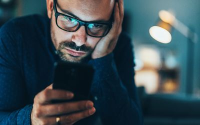 Man looking irritated at his phone