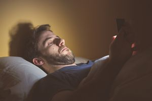A man with facial hair lies in bed looking at his smart phone screen.