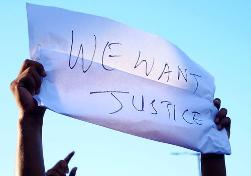 "person holding ""we want justice"" sign"