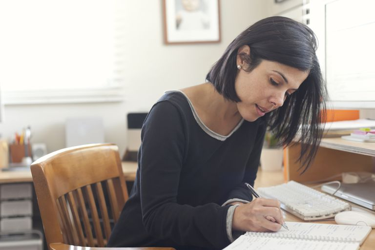 woman writing at home office desk