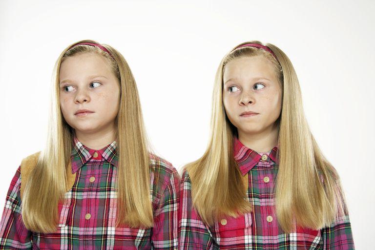Twin girls looking uncomfortable