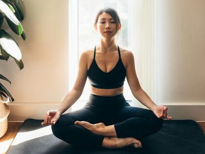Full length shot of a young Asian woman with eyes closed and crossed legs, feeling calm, sitting on a yoga mat near the window.