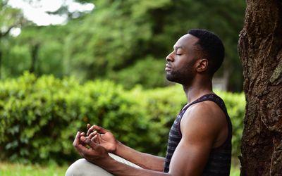 Black man meditating outside
