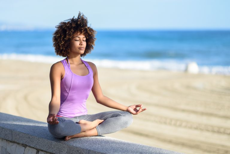 Young Woman Meditating On Retaining Wall At Beach