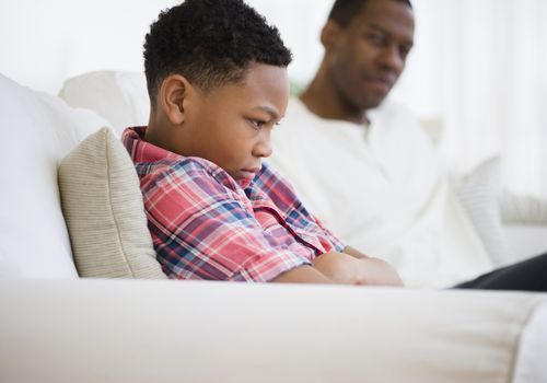 Upset young boy sitting next to his father
