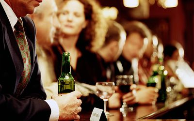 PENSIVE MAN IN BAR WITH PEOPLE