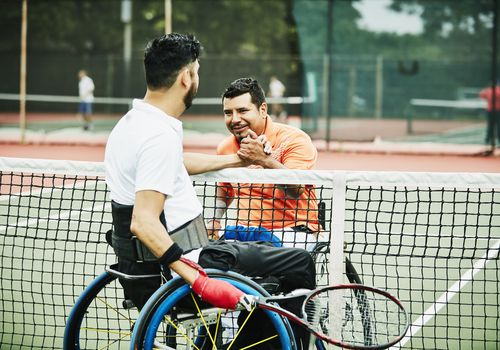 two adaptive athletes shaking hands after a tennis match