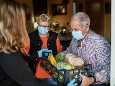Woman delivering groceries to an older couple wearing face masks
