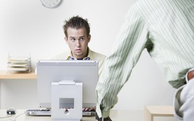Businessman leaning on desk talking to coworker