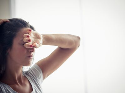 Woman not feeling well with hand on head