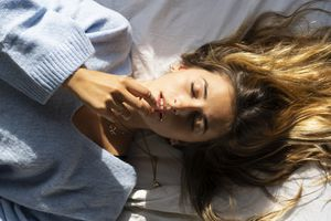 Portrait of beautiful young woman lying in bed with closed eyes