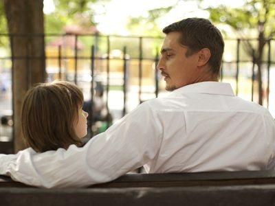 Father and daughter talking on park bench