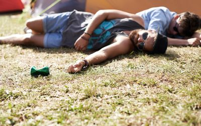 two men passed out in the grass at an outdoor festival