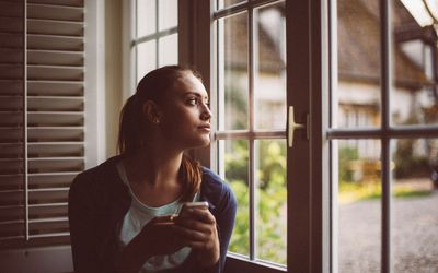 Detached woman looking out the window with no emotion.