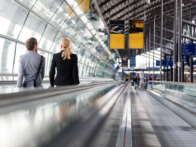 man and woman on moving walkway at airport