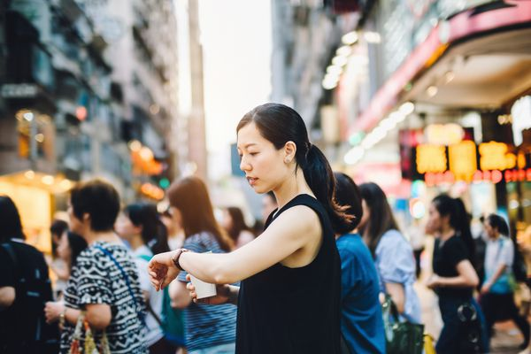 Busy woman looking at watch on street