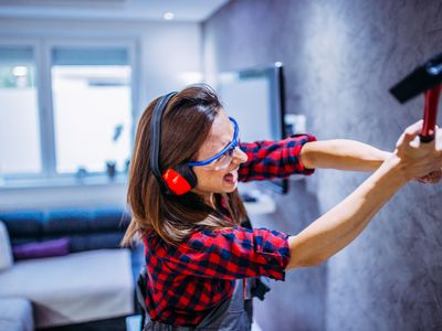 Woman smashing wall with hammer: do anger rooms help or hurt?