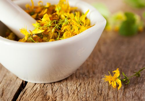 Yellow flowers in a white mortar with pestle