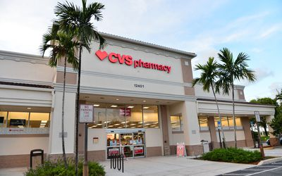 A beige CVS store entrance stands between two rows of palm trees.