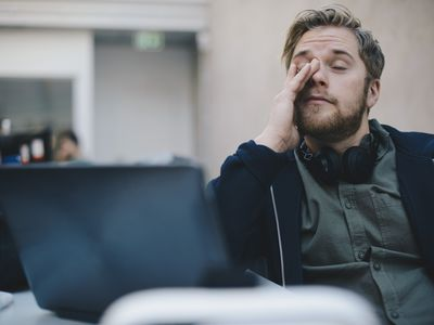 Fatigued man rubbing his eyes
