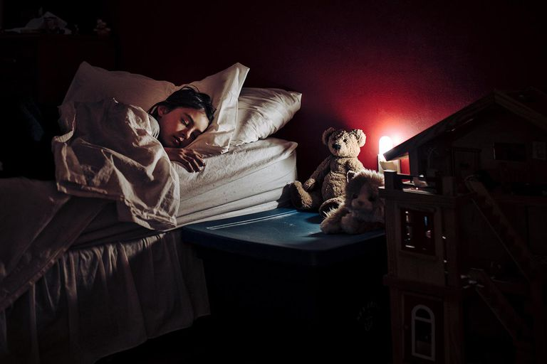 Girl asleep in bed lit only by night light.
