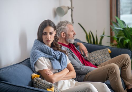 Young woman and bearded man sitting on a sofa