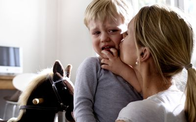 toddler crying in mother's arms