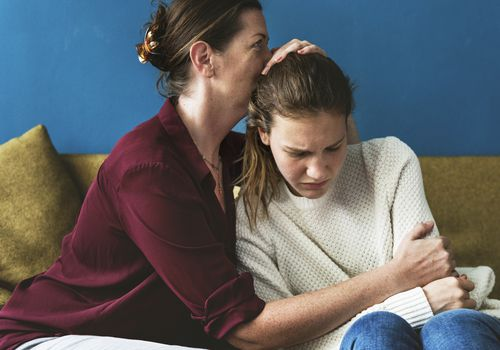 Mother embracing an upset teen girl on the couch