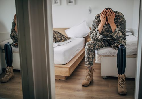 veteran sitting on the edge of the bed with his head in his hands