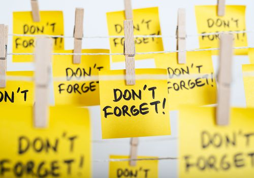 "yellow notes saying ""Don't forget!"" affixed to line with clothespins"