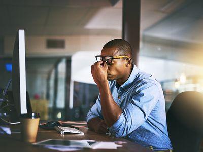 Man sitting at desk feeling stressed.