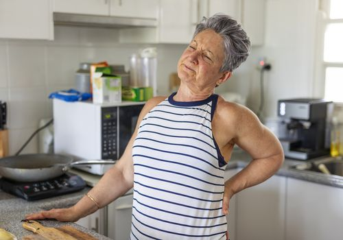 Older woman with chronic pain in kitchen