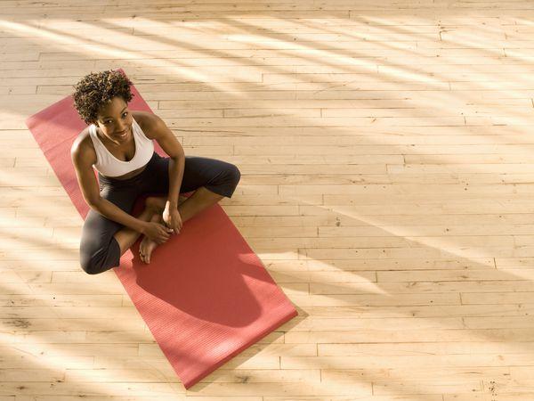 Woman sitting on yoga mat.