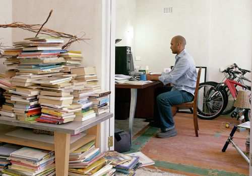 Man sitting at a cluttered desk with books piled in the hall