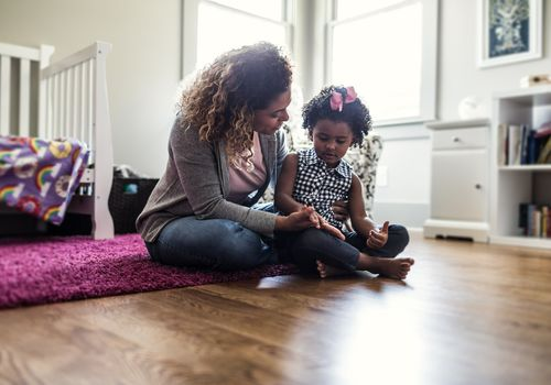 Mother sitting on the floor playing with a young child.