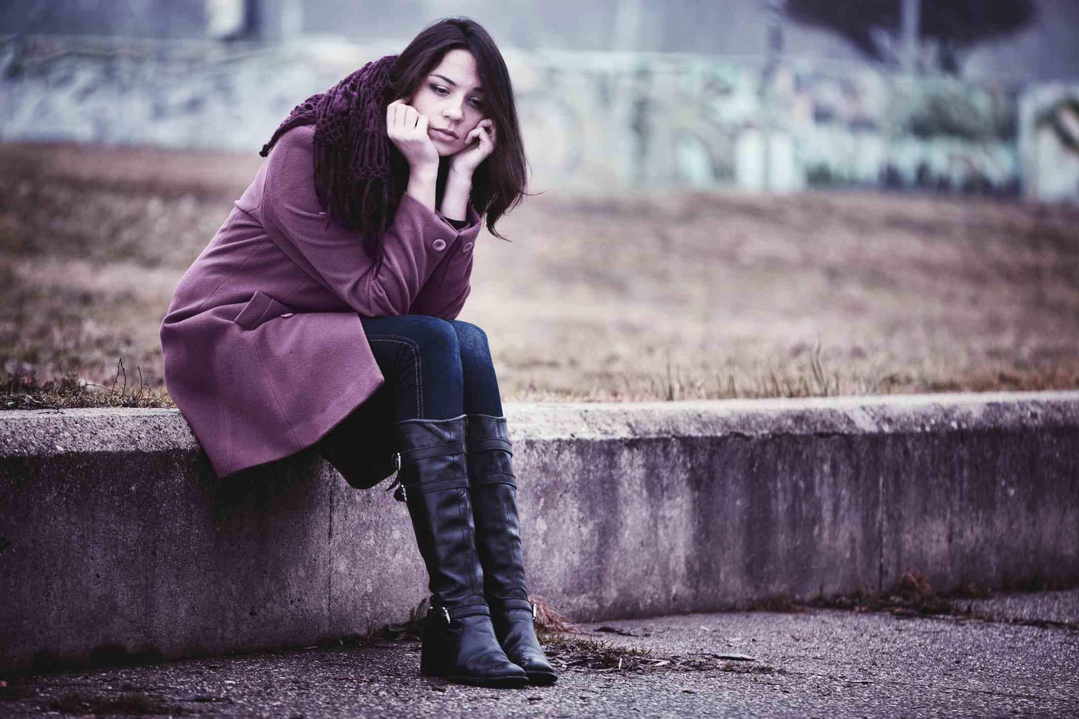 lonely-girl-by-wall-sitting-AlexanderNovikov.jpg