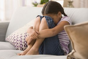 A sad young girl hiding her face on the couch