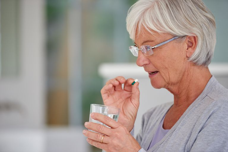 Shot of a senior woman about to take a pill