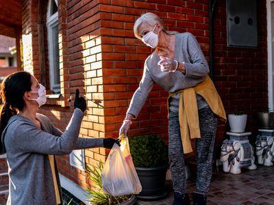 Female volunteer bringing groceries to a senior woman at home under quarantine because of coronavirus.