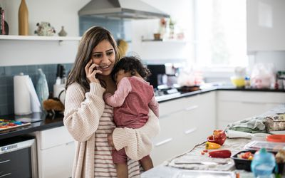 Woman standing in kitchen, holding child and talking on the phone
