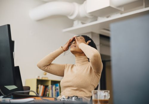 stressed woman with head in hands sitting in an office