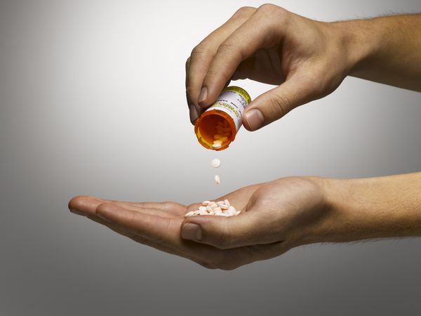 One hand holding a prescription pill bottle and pouring it into the other hand