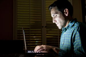 Person looking at their computer late at night in the dark