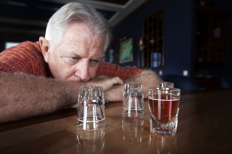 Senior man looking at shot glass at a bar