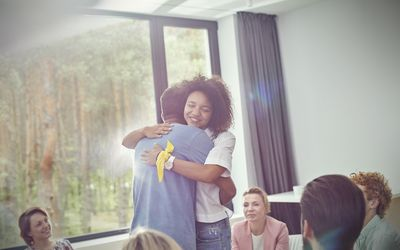 Man and woman hugging in group therapy session
