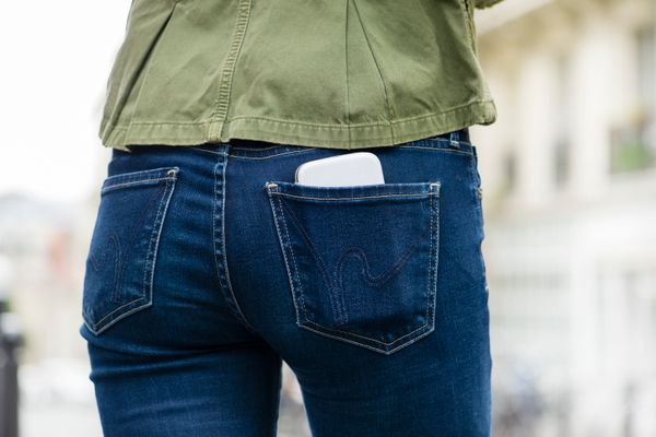 Close-up of woman wearing jeans from behind with cell phone in her back pocket
