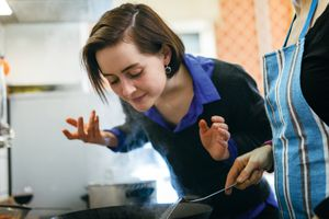 woman smelling food from a pan on the stove