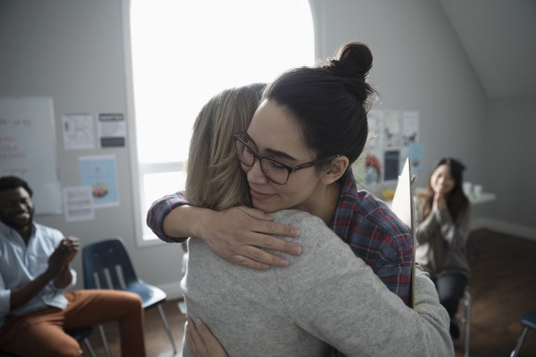 Women hugging in support at support group in community center