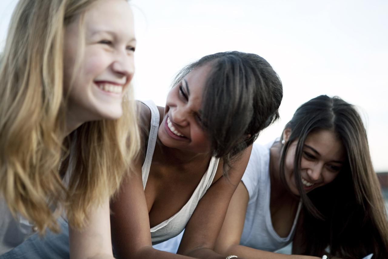 three teenage girls (16-18) laughing